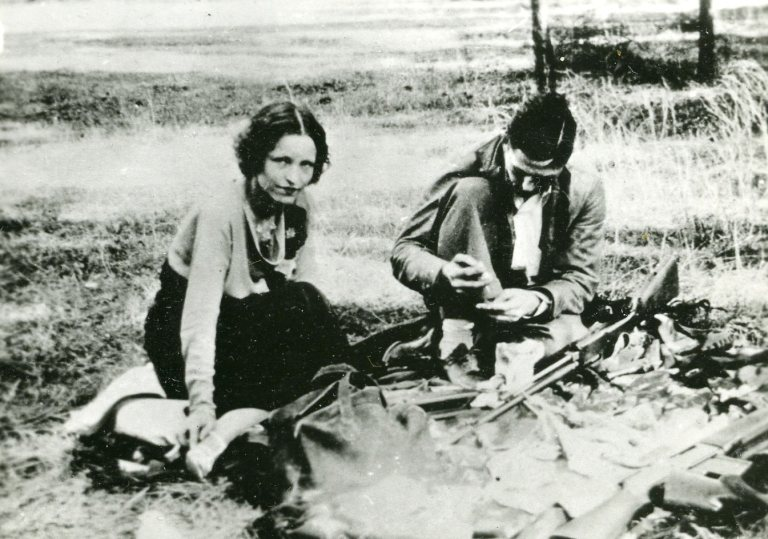 Bonnie & Clyde sitting on tarp, Clyde cleaning rifle