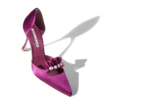 Image of woman's purple/pinkish stiletto, decorated with fake pearls and ruffles on top