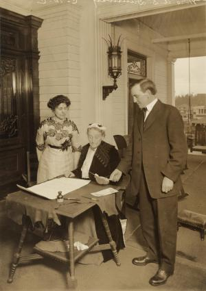 Abigail Scott Duniway signing first Equal Suffrage Proclamation ever made by a woman. Oregon Governor Oswald West, who had signed the Proclamation is shown looking on, and acting President Dr. Viola M. Coe is standing near.