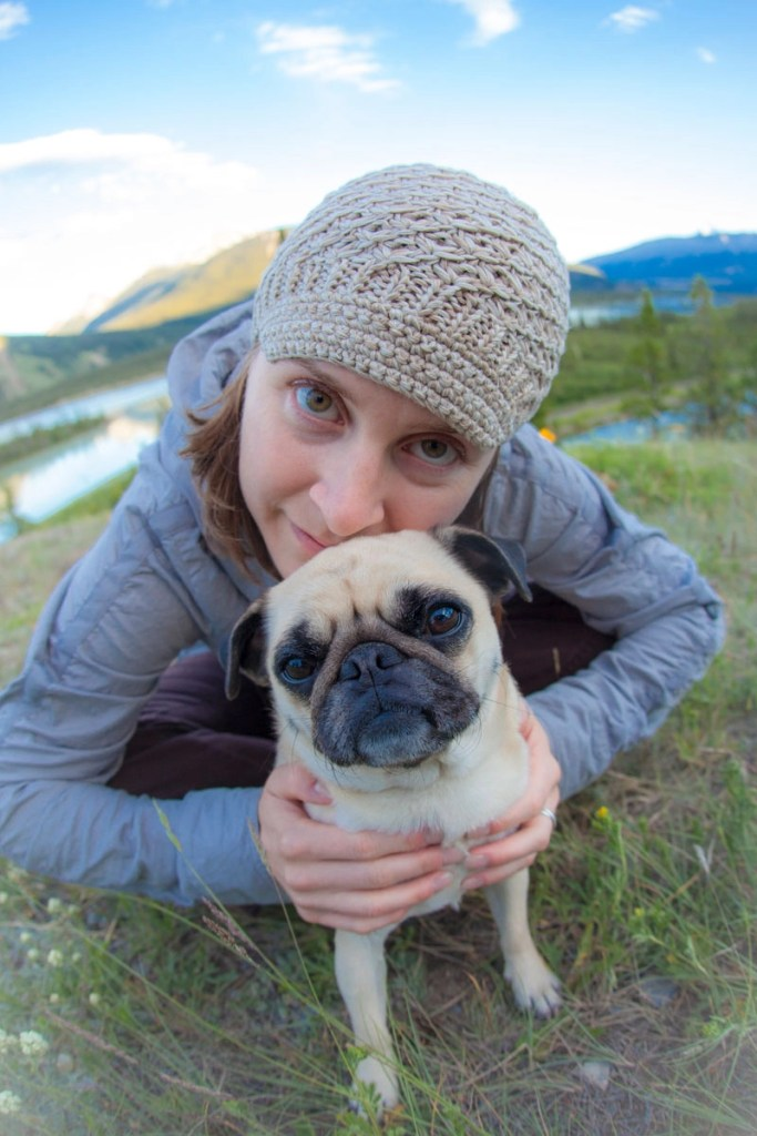 Girl cuddling pug in the mountains having an adventure