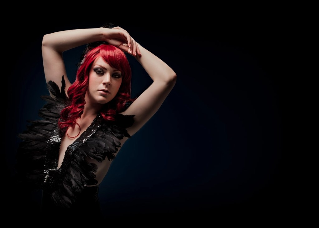 Professional portrait of latex fashion model with red hair