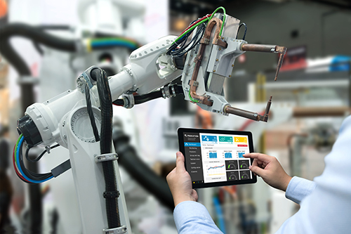Engineer hand using tablet, heavy automation robot arm machine i
