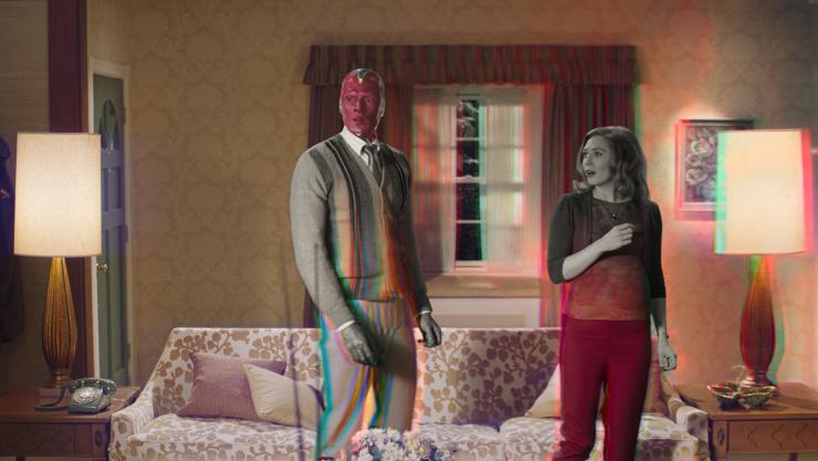 Wanda and Vision stand in a living room, half in black-and-white and half in color