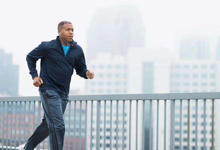 african american man running outside with cityscape background
