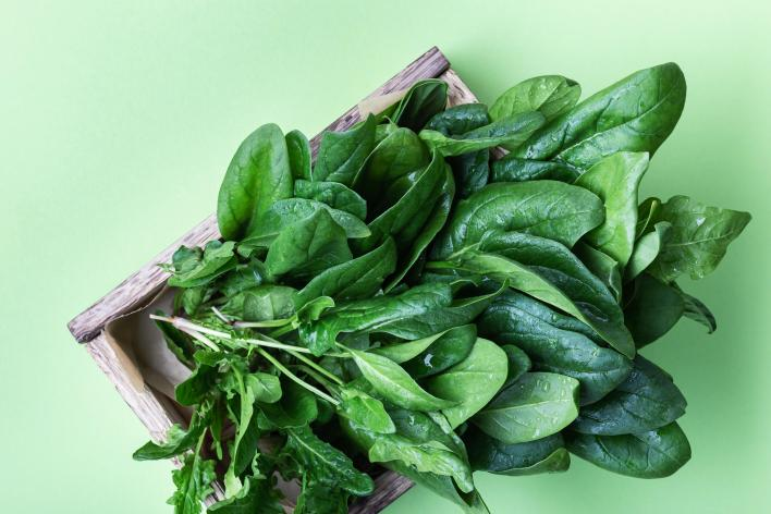 spinach in a wooden crate on a green background
