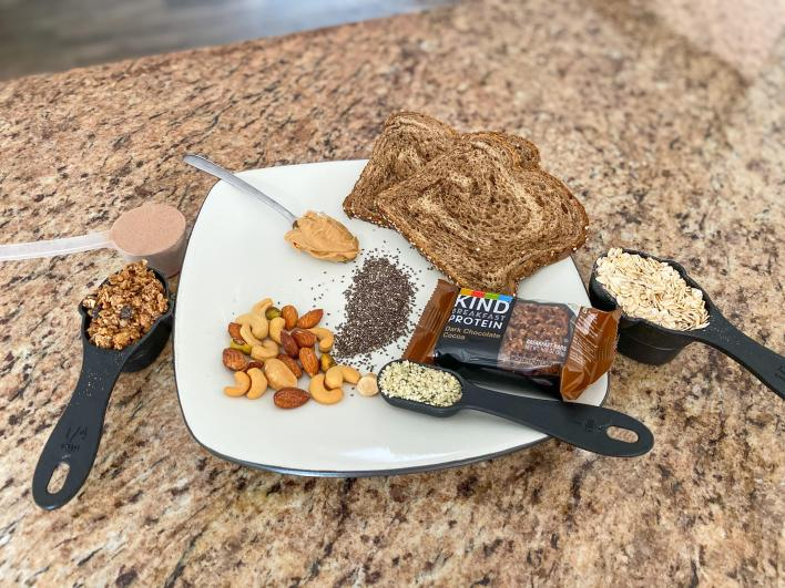 a spread of food containing granola, protein powder, hemp seeds, peanut butter, chia seeds, bread, oats, and a granola bar depicting protein options for vegans