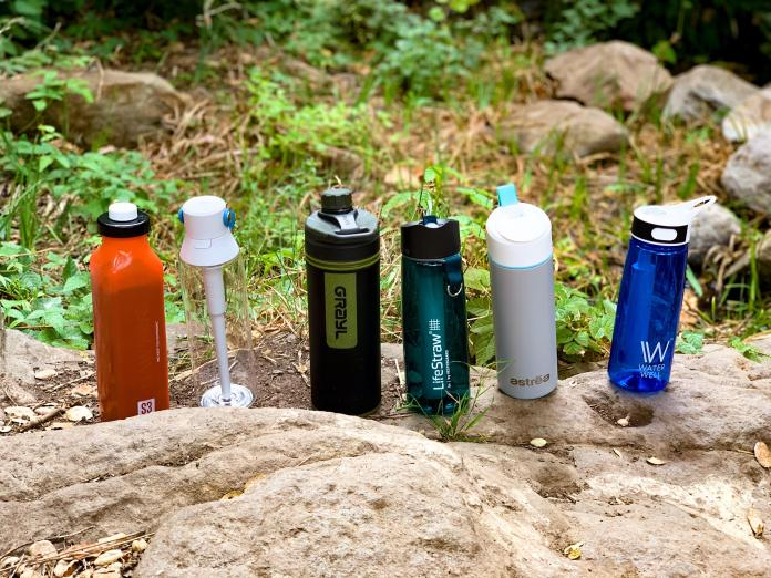 Six filtered water bottles lined up outdoors.