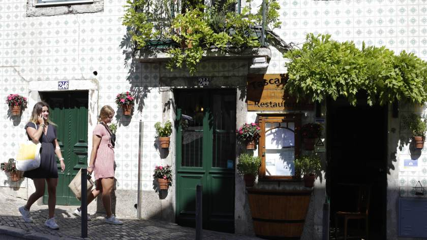 Women pass by restaurant in Lisbon;  Portugal reopens borders for Brazilian tourists