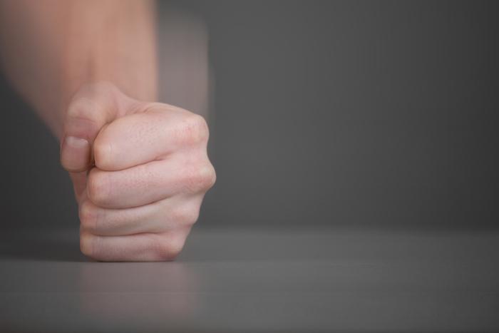 personne qui tape du poing sur la table