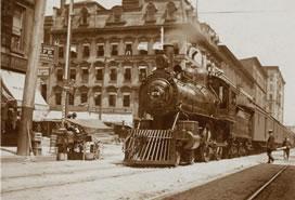 sepia photo of train through city