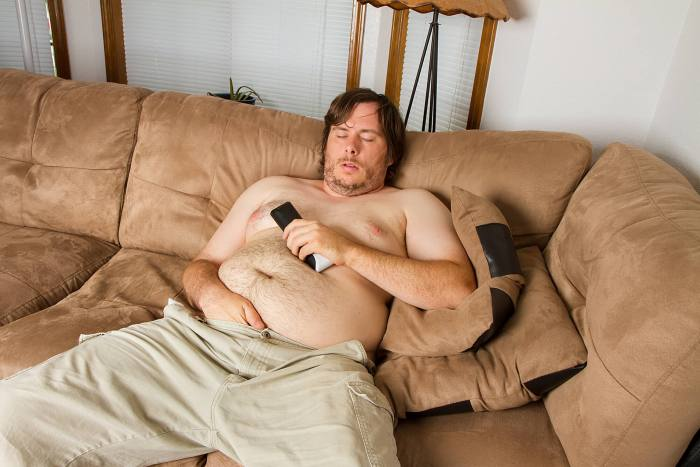 shirtless guy asleep on couch - What Suze Orman Got Wrong About the FIRE Movement