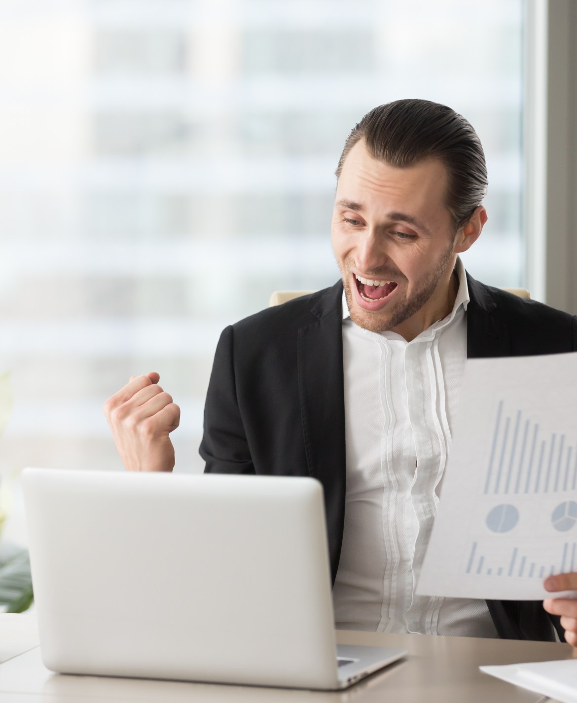 Happy handsome project manager in office celebrates and screams with happiness, looking at laptop screen and holding positive financial report. Great news on stock investment, finance victory concept.