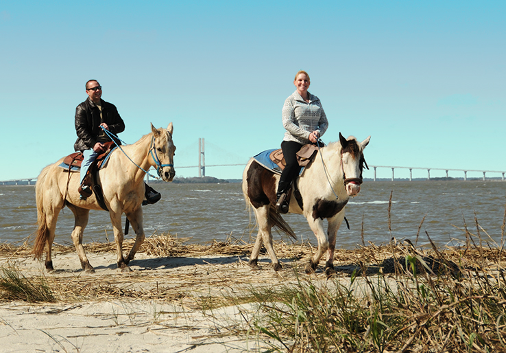 Two people riding horses on Jekyll Island.