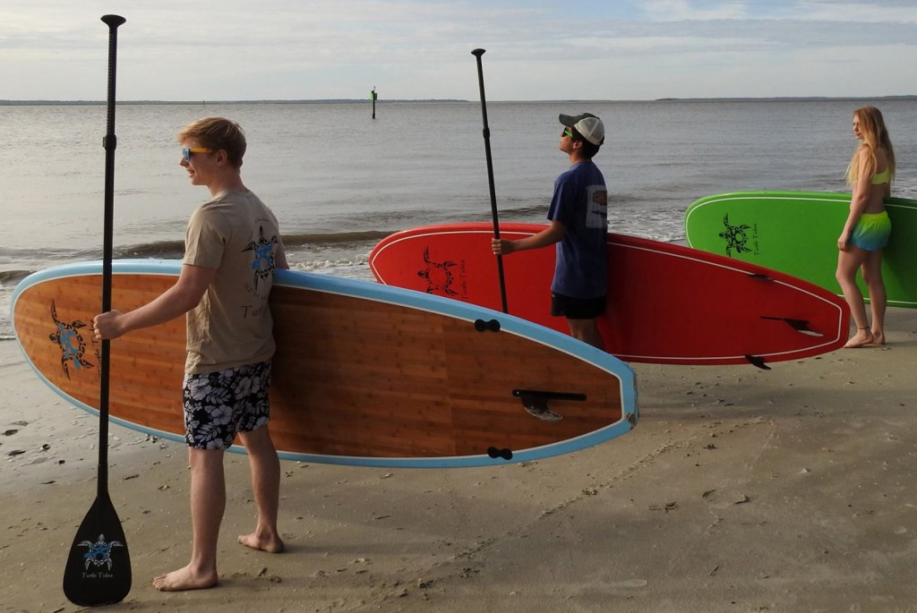 Picture of kids ready to hit the water on their Turtle Tides paddle boards.