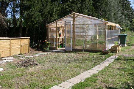 Vista exterior del invernadero, compostero y depósito de agua