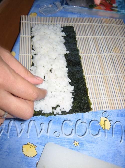 Tomamos un puñado de arroz y con los dedos lo distribuimos por toda la hoja de Nori creando una capa uniforme para que sea más fácil esparcir humedecer los dedos.