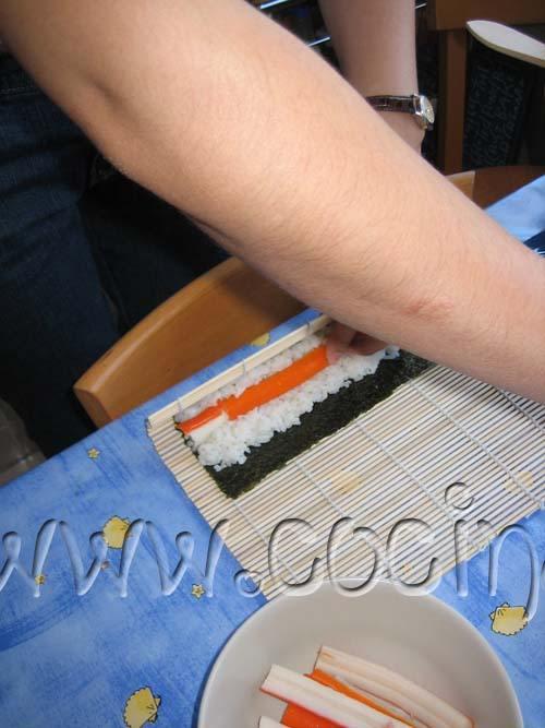 Ahora enrolla el sushi utilizando la estera de madera, presionando suavemente para que tome la forma adecuada.