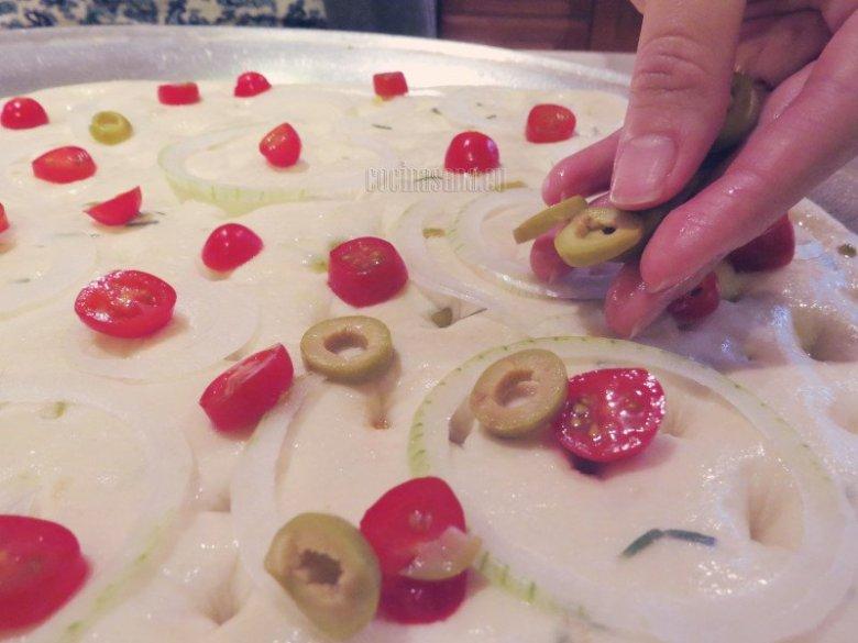coloca la cebolla, el tomate, aceitunas, la sal y el romero sobre tu hogaza