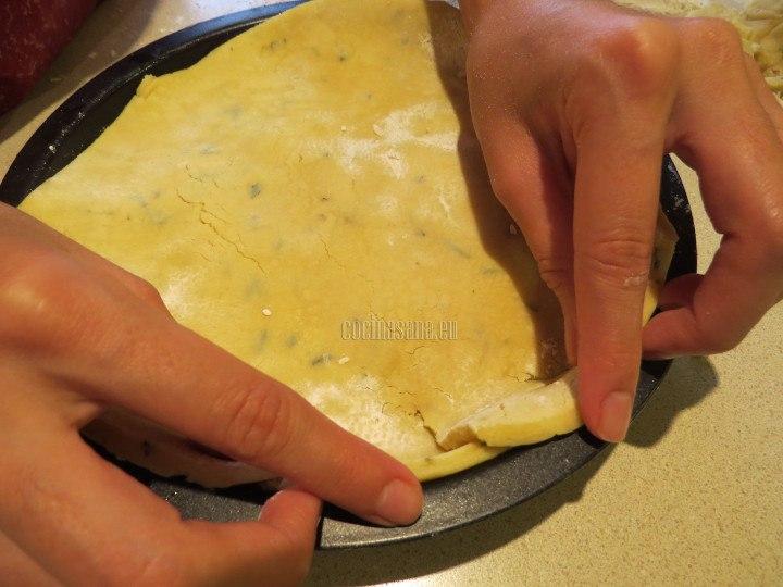 Cubrir con la masa el molde, cubriendo muy bien los bordes del molde. engrasar ligeramente para evitar que se pegue