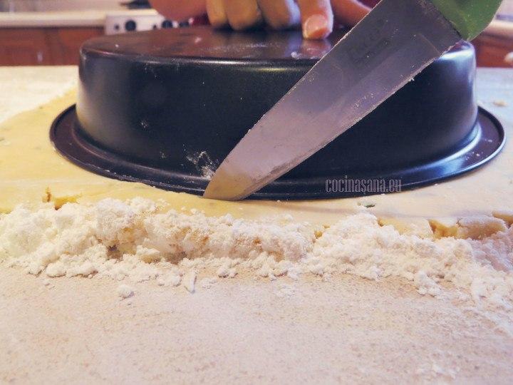 Recortar la masa siguiendo la forma del recipiente utiliza la punta de un cuchillo o un cortador de pizza