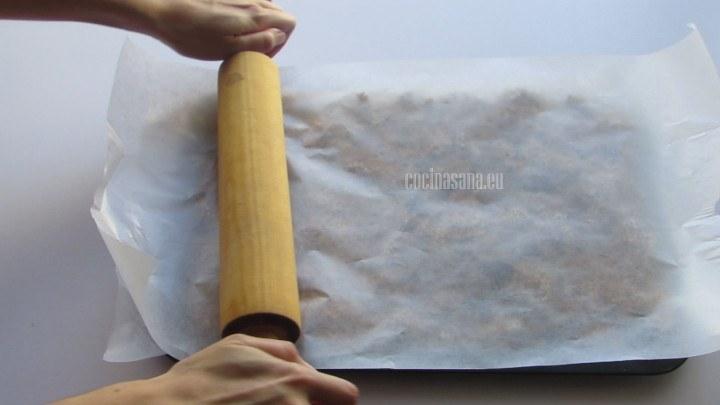 Aplanar con la ayuda de un rodilla o una botella, colocando un papel encerado sobre la mezcla para lograr que se compacte la preparación
