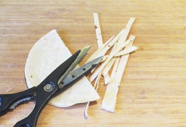 Cortar las tortillas con la ayuda de unas tijeras o con un cuchillo en tiras delgadas.