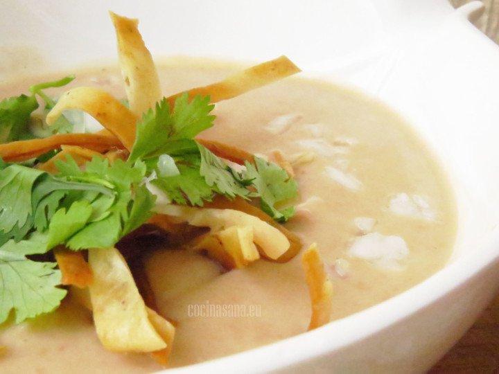 Servir la crema de frijol con la cebolla, cilantro y tortillas fritas.