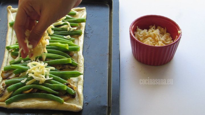 Espolvorear el queso rallado sobre la tartaleta, puedes emplear diferentes variedades de queso para añadir a esta receta.