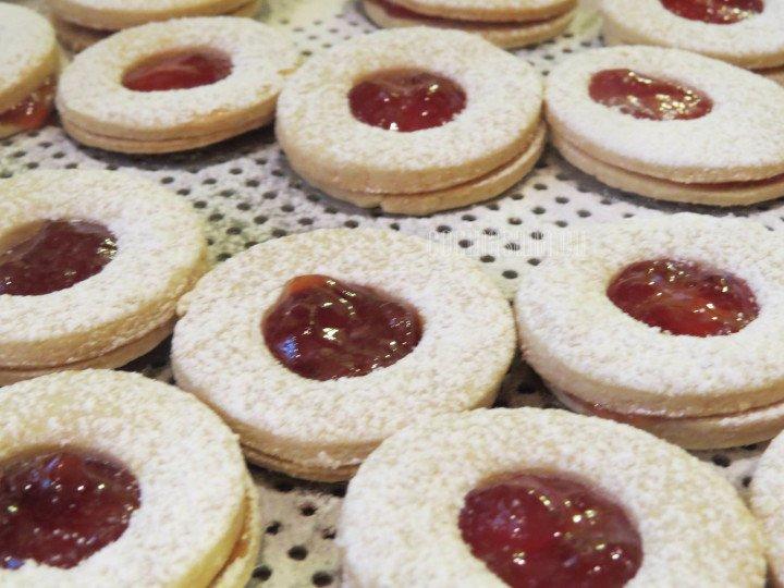 Espolvorear azúcar glass sobre las galletas, también puedes espolvorear primero las tapas y después colocar el relleno