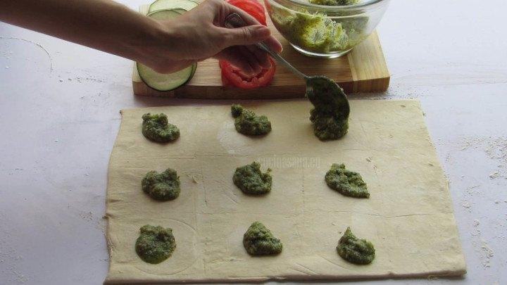 Extender la masa de hojaldre y colocar encima el pesto como si se prepararan ravioles para que puedan cortarse al momento de porcionar las tartaletas