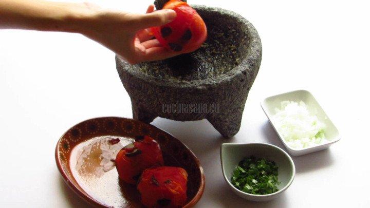 Triturar el ajo, sal, chile, tomate