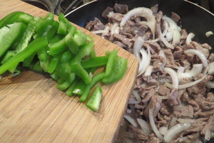 Añadir la cebolla y el pimiento verde a la carne