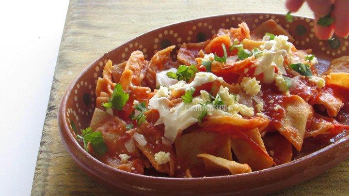 Servir los chilaquiles con el cilantro el queso y la crema como guarnición