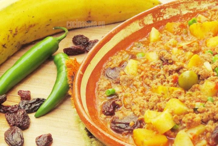 Picadillo elaborado con carne de res, plátano macho, pasas, guisantes y otras verduras.