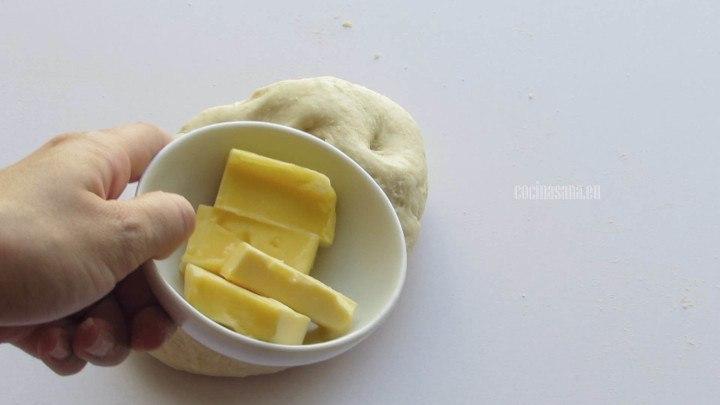 Añadir la mantequilla a la masa y continuar amasando hasta que se incorpore por completo