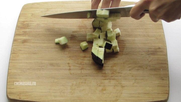 Picar la berenjena en cubos, no te olvides de remojarla antes en agua con un poco de sal para extraer el sabor amargo de la berenjena.