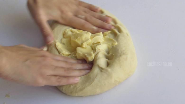 Agregar la mantequilla e incorporar en la masa poco a poco con tus manos o una batidora.