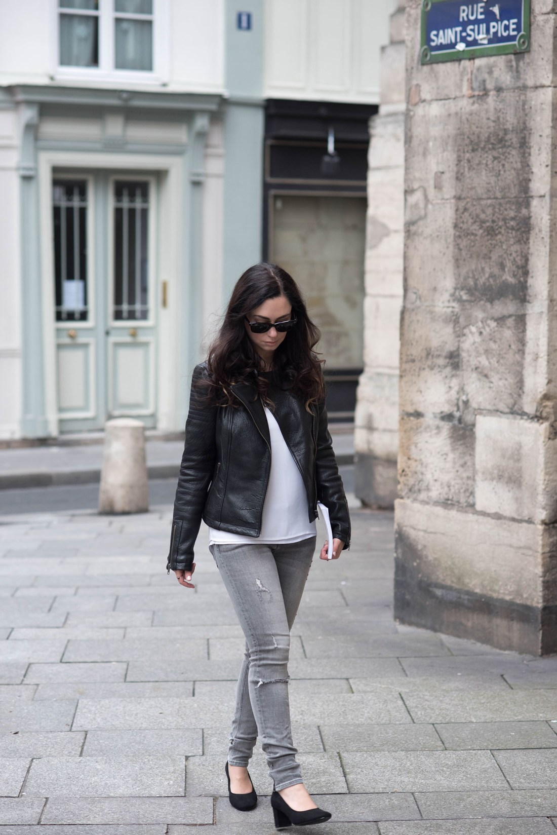 Lifestyle blogger Cee Fardoe of Coco & Vera walks in Paris wearing a leather jacket and Express Barcelona tank
