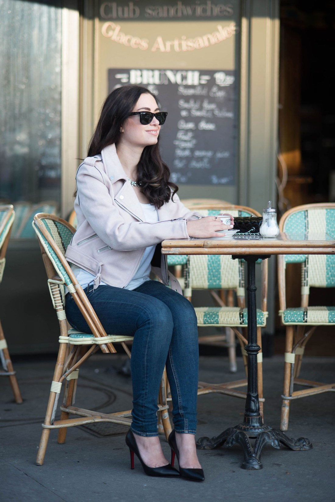 Fashion blogger Cee Fardoe of Coco & Vera sits at the Esmerelda Cafe in Paris wearing Rag & Bone jeans and Christian Louboutin heels