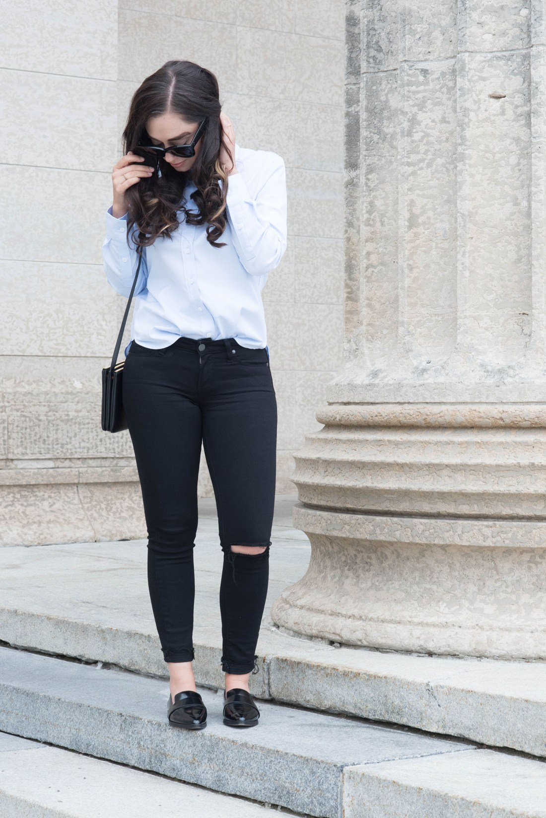 Fashion blogger Cee Fardoe of Coco & Vera stands at the Manitoba Legislature wearing Charles & Keith Loafers and Paige Denim jeans
