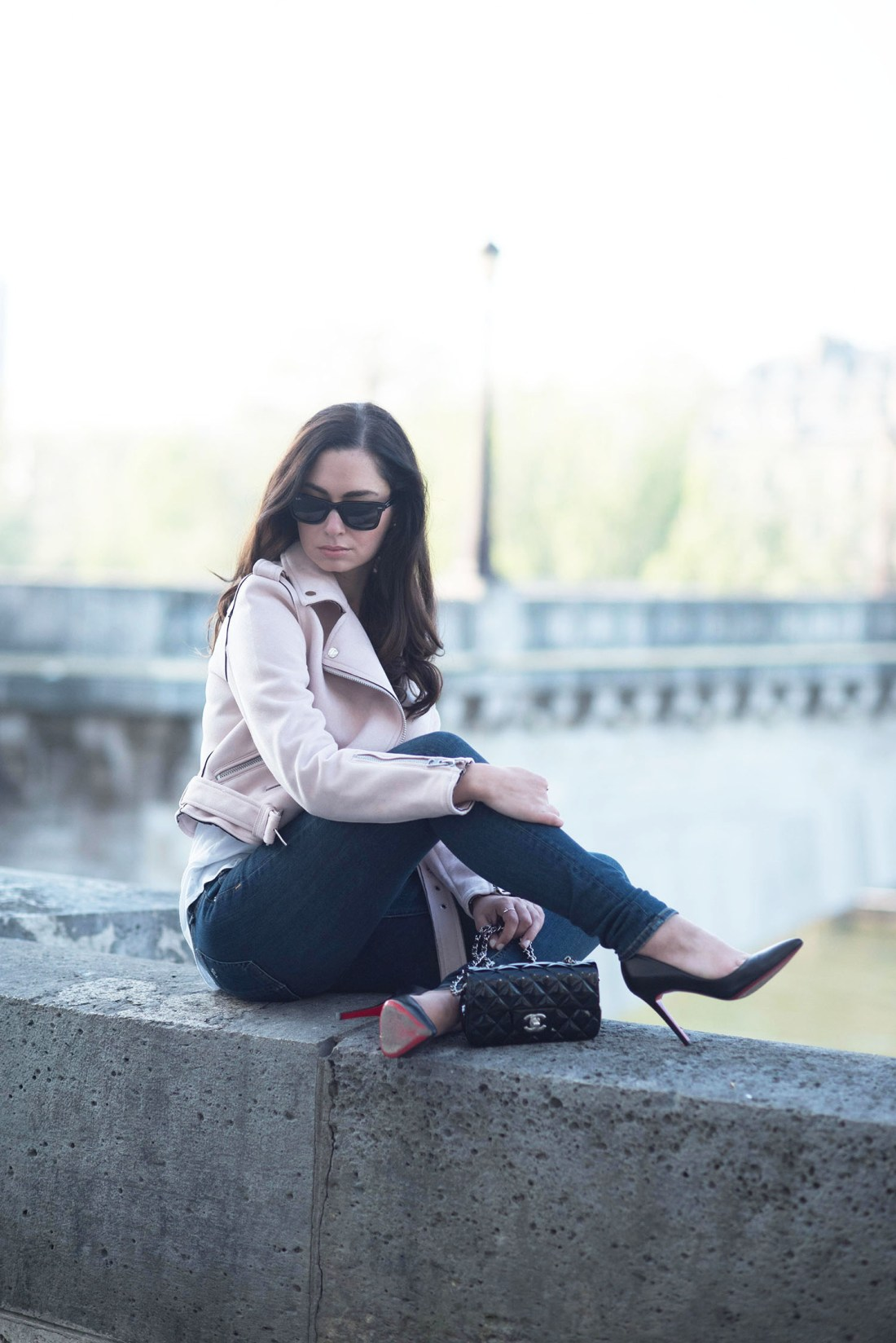 Style blogger Cee Fardoe of Coco & Vera sits on the quad in Paris wearing Christian Louboutin Pigalle pumps and pink Zara jacket