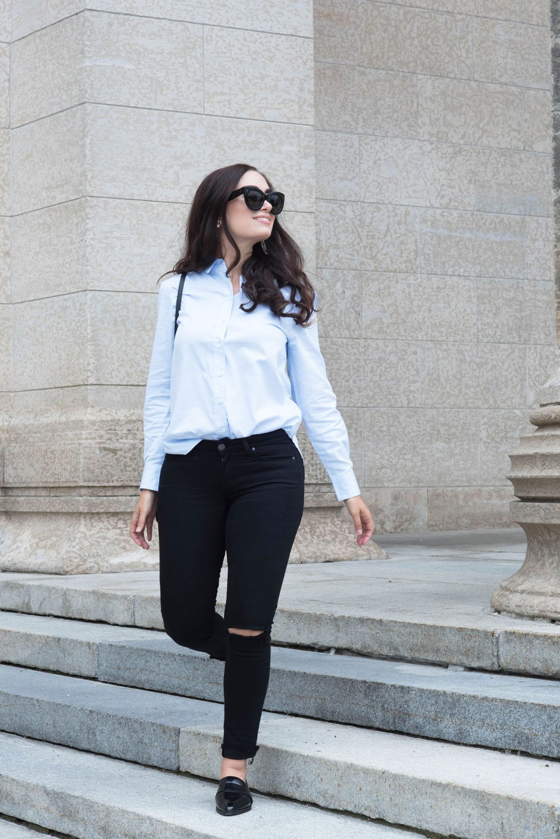 Canadian fashion blogger Cee Fardoe of Coco & Vera walks down a flight of stairs wearing an Equipment cotton blouse and Paige Denim jeans