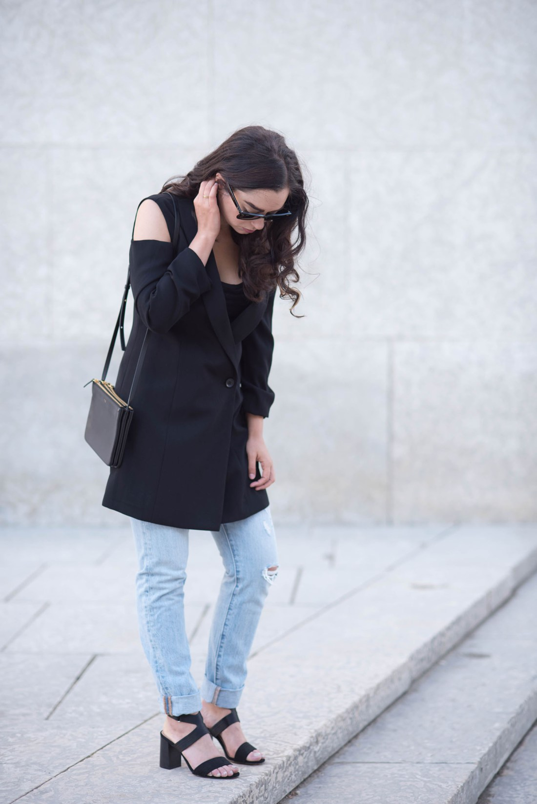 Style blogger Cee Fardoe of Coco & Vera stands wearing Levis 501 skinny jeans and an Ever New coat