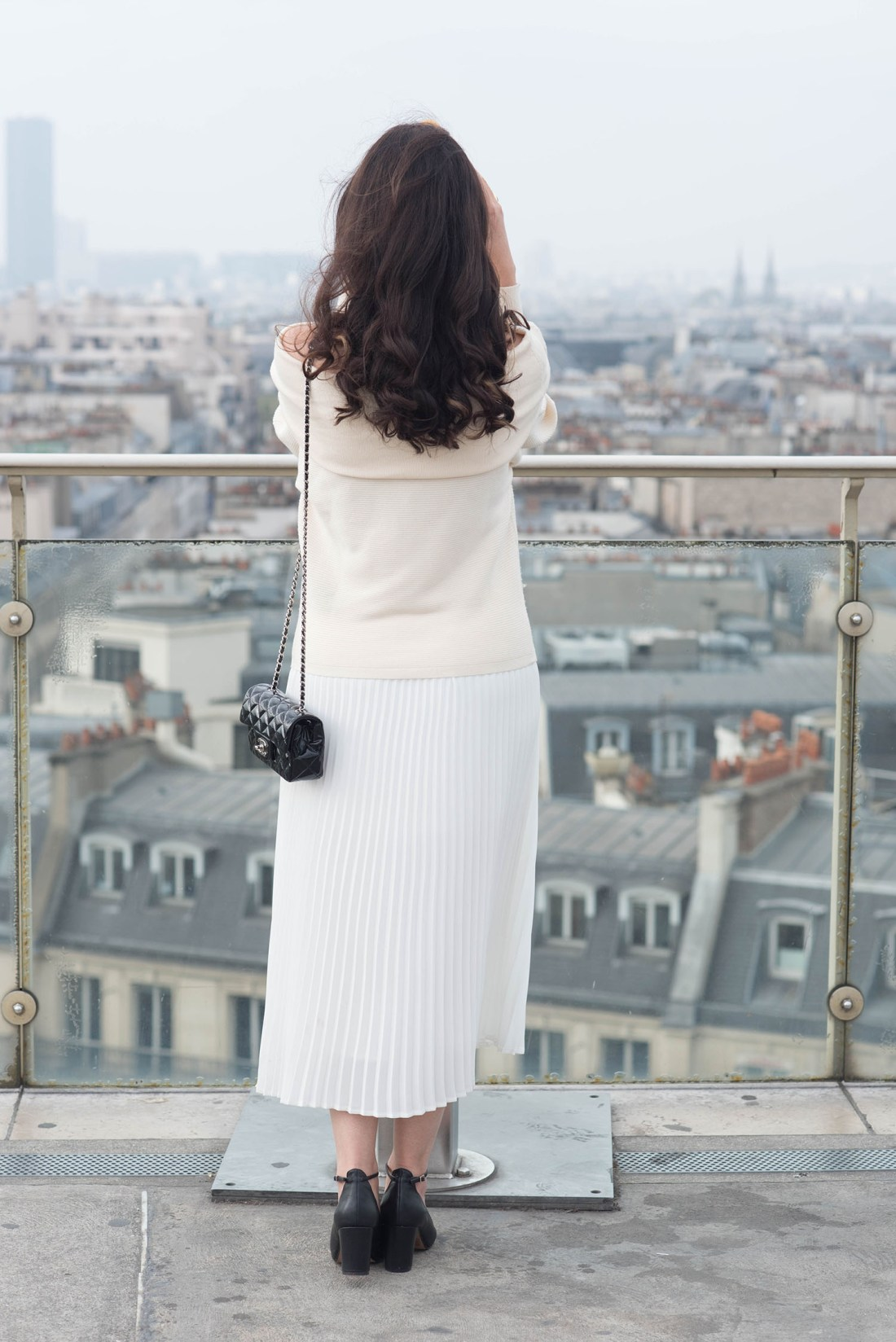 Brunette fashion blogger Cee Fardoe of Coco & Vera looks out over the rooftops of Paris wearing a white Aritzia skirt and carrying a black Chanel handbag