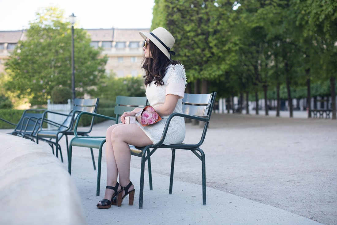 Canadian fashion blogger Cee Fardoe of Coco & Vera sits in the Palais Royal garden wearing a Floriane Fosso dress and Le Chateau sandals