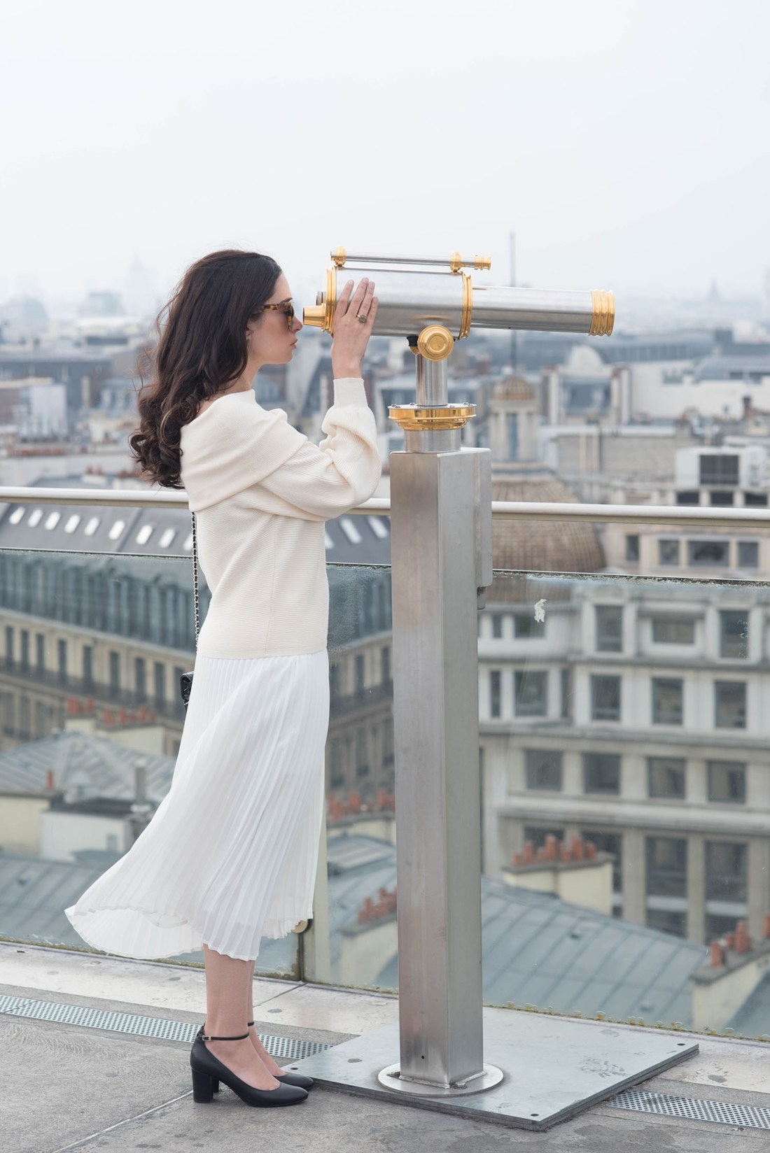 Fashion blogger Cee Fardoe of Coco & Vera stands on Paris rooftop looking out a telescope wearing a Zara sweater and Aritzia pleated skirt