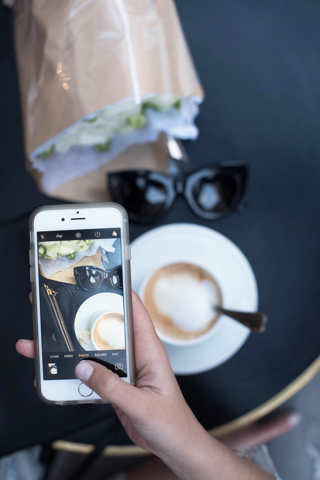 Fashion blogger Cee Fardoe of Coco & Vera captures a photo of her morning coffee at Maison Marie in Paris with her iPhone 6s