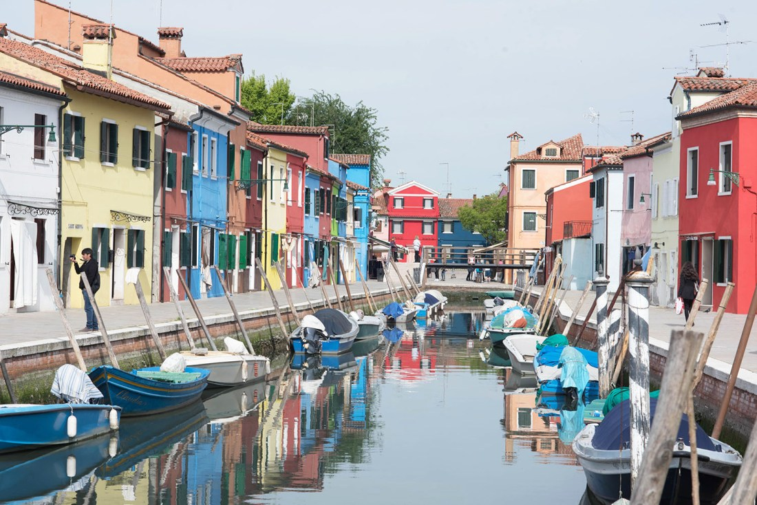 Brightly coloured houses line the canal on the island of Burano in Italy, captured by travel blogger Cee Fardoe of Coco & Vera