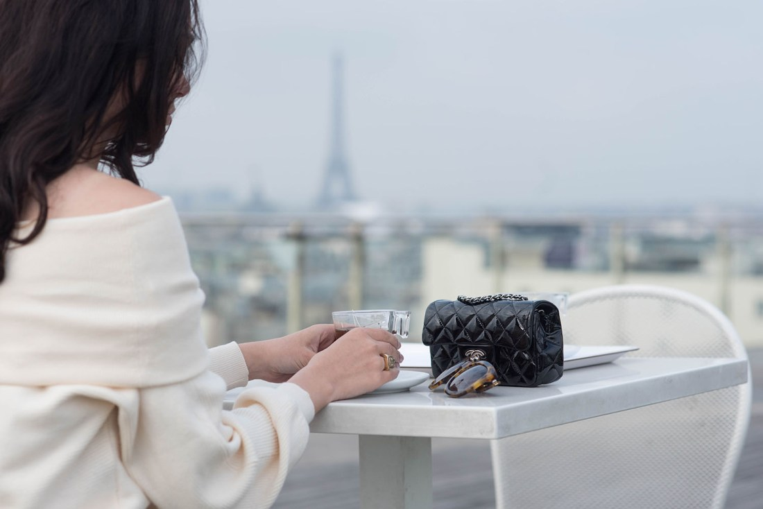 Details of style blogger Cee Fardoe of Coco & Vera at Printemps in Paris with a view of the Eiffel Tower, drinking tea with her Chanel handbag