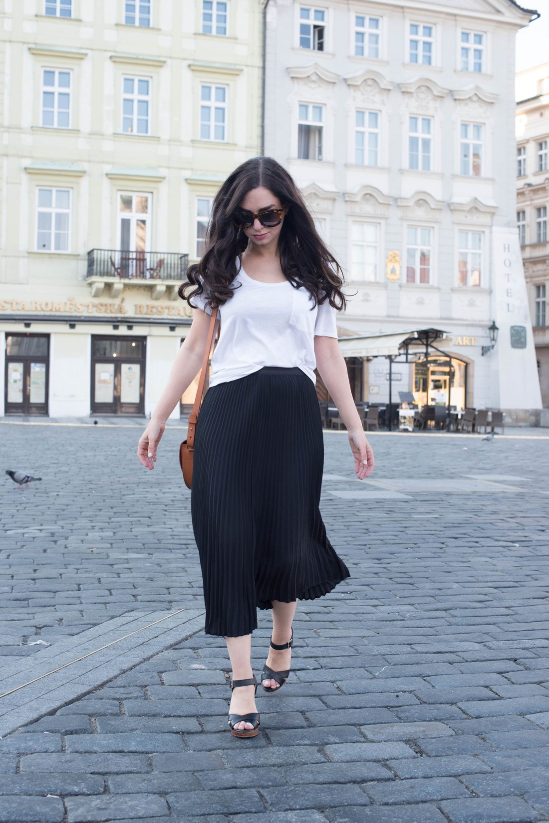 Fashion blogger Cee Fardoe of Coco & Vera walks through the Old Town Square in Prague wearing a white Aritzia tee, Le Chateau leather sandals and Anine Bing sunglasses